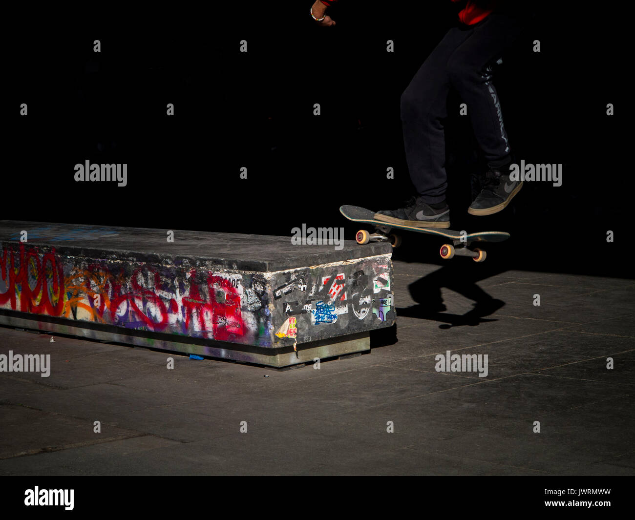 A skateboarder performs a trick in the evening sunshine - Stock Image