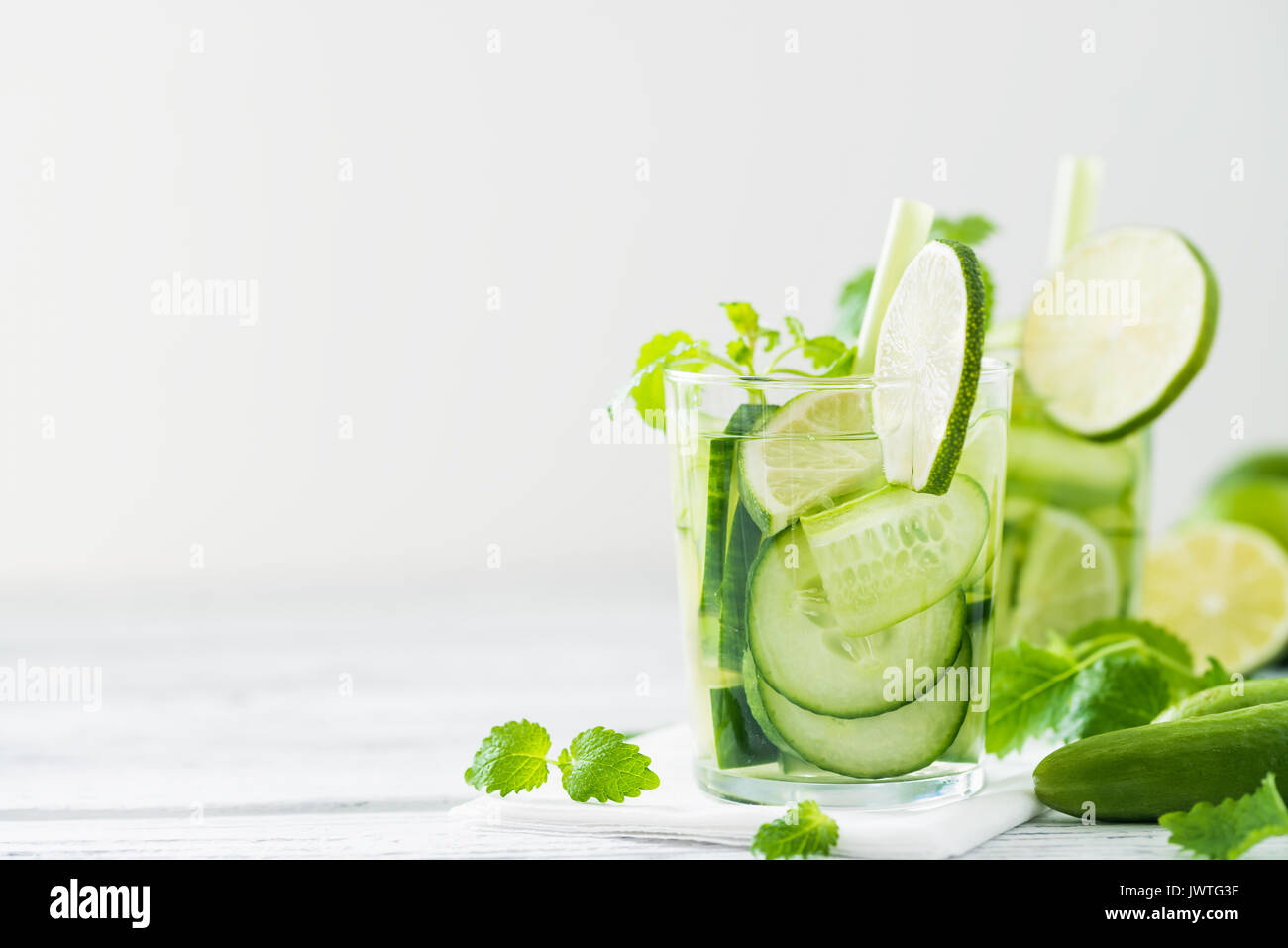 Refreshing drink with cucumber, lime, mint. Detox concept. White rustic table. Copy space - Stock Image