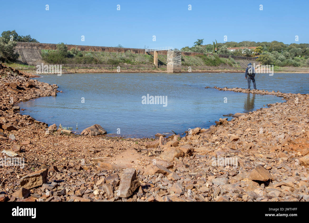 Man overlooking the Roman Dam of Cornalvo. This dam was declared National Monument on Dec 13th 1912, and it is still - Stock Image