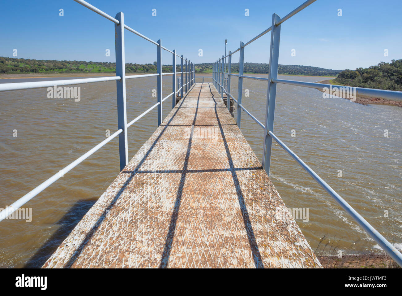 Modern footbridge attached to Dam of Cornalvo Reservoir. This monument is still in use nowadays, Extremadura, Spain - Stock Image