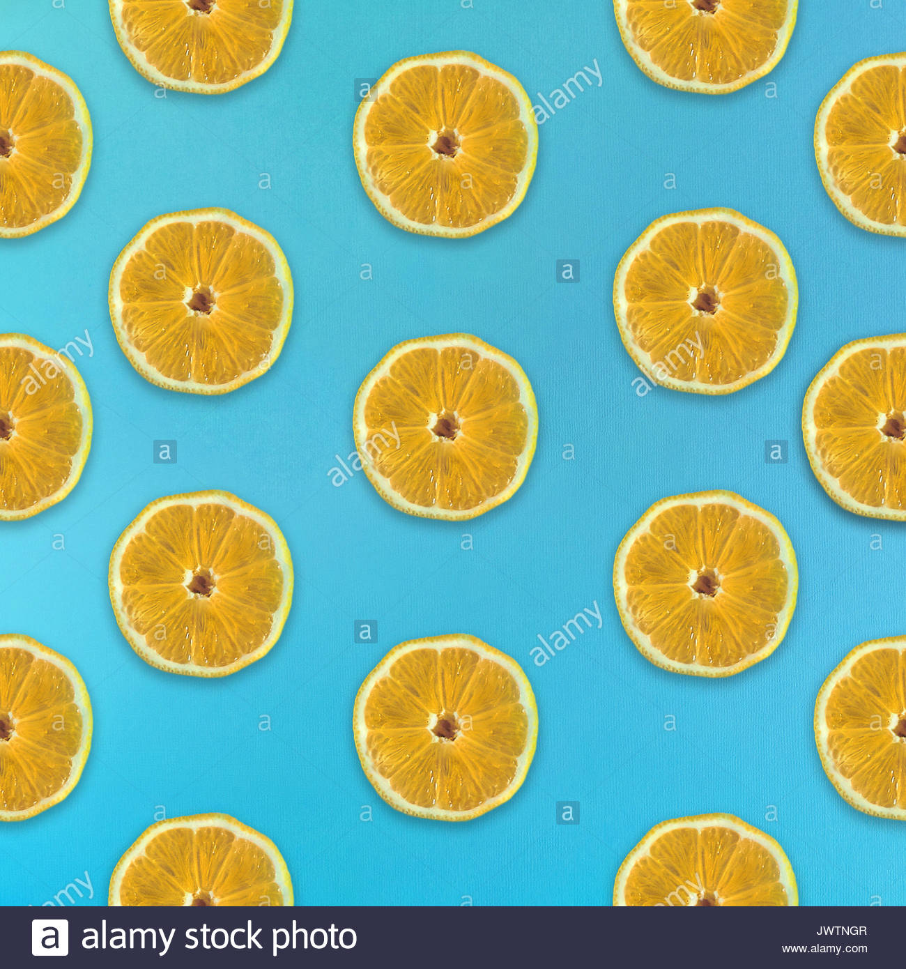 Fruity pattern in flat lay Half of lemon on blue background Top view Trendy colorful flat lay pattern of lemon fruit - Stock Image