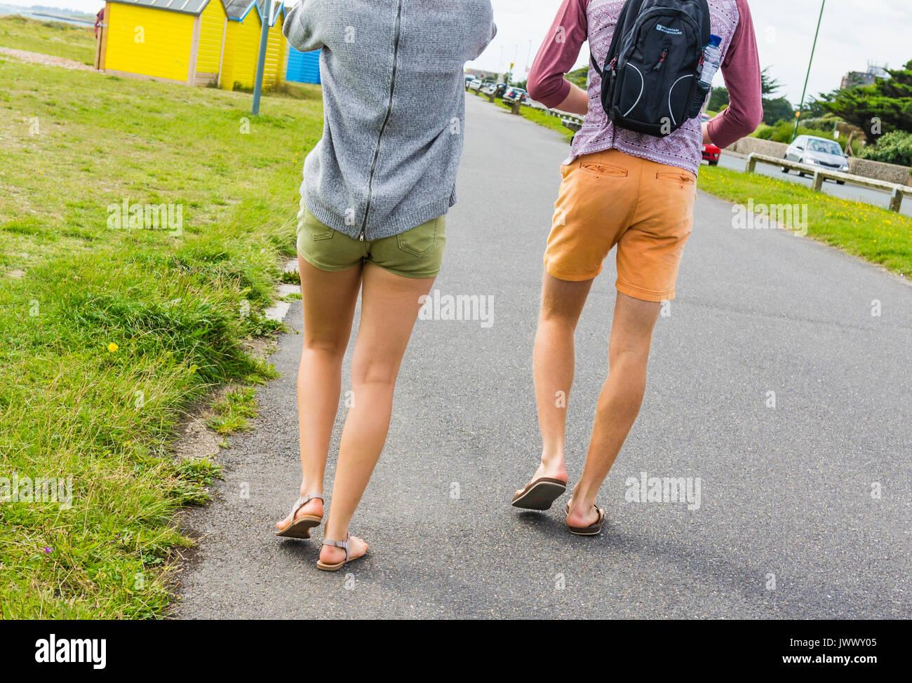a-young-couple-walking-along-the-promenade-wearing-shorts-showing-JWWY05.jpg