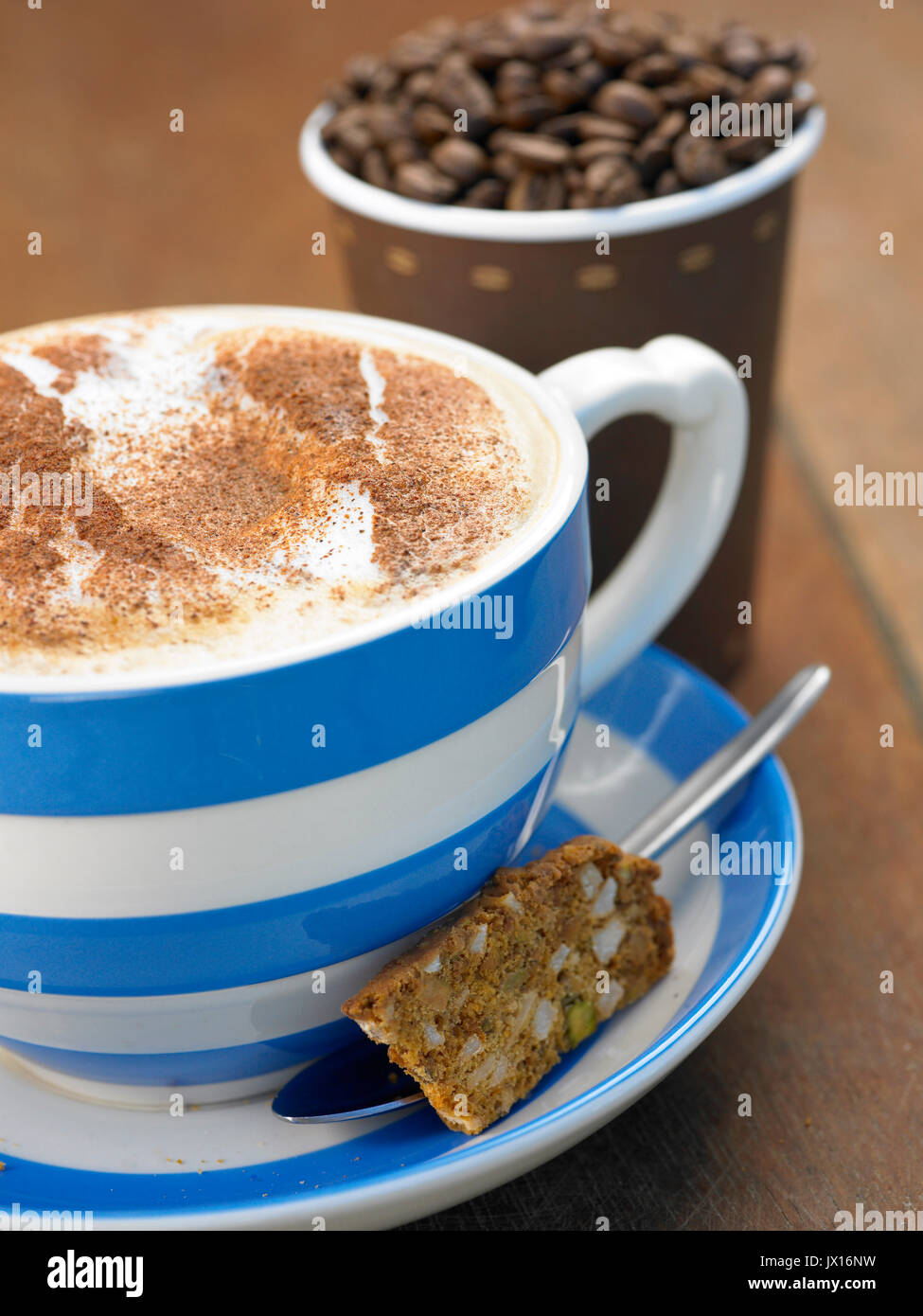 cappuccino coffee in large blue and white mug with cinnamon with takeaway cup full of beans ,newspaper and biscotti - Stock Image