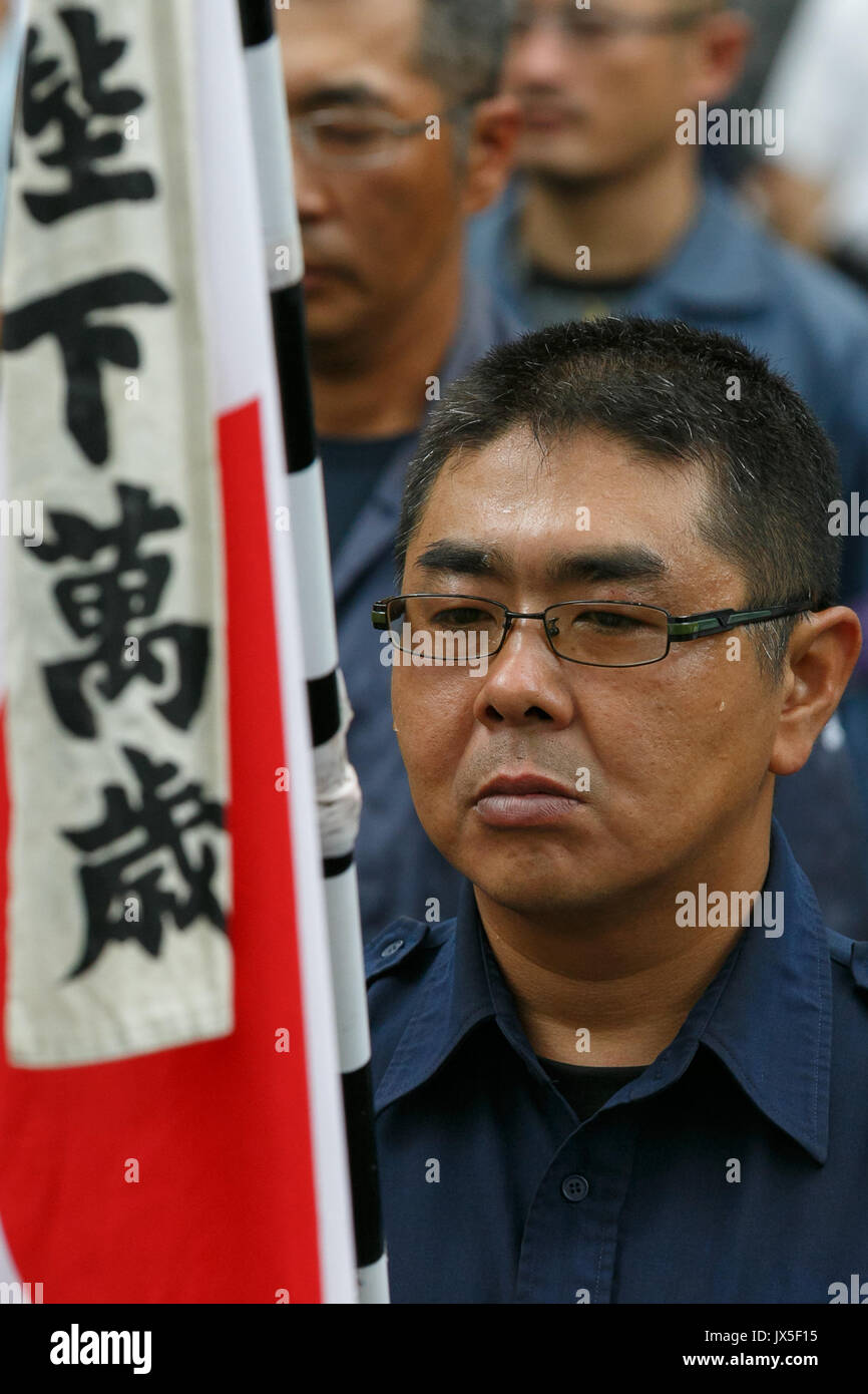 Tokyo, Japan. 15th Aug, 2017. A Japanese nationalist dressed in military uniform holds a war flag of the Imperial - Stock Image