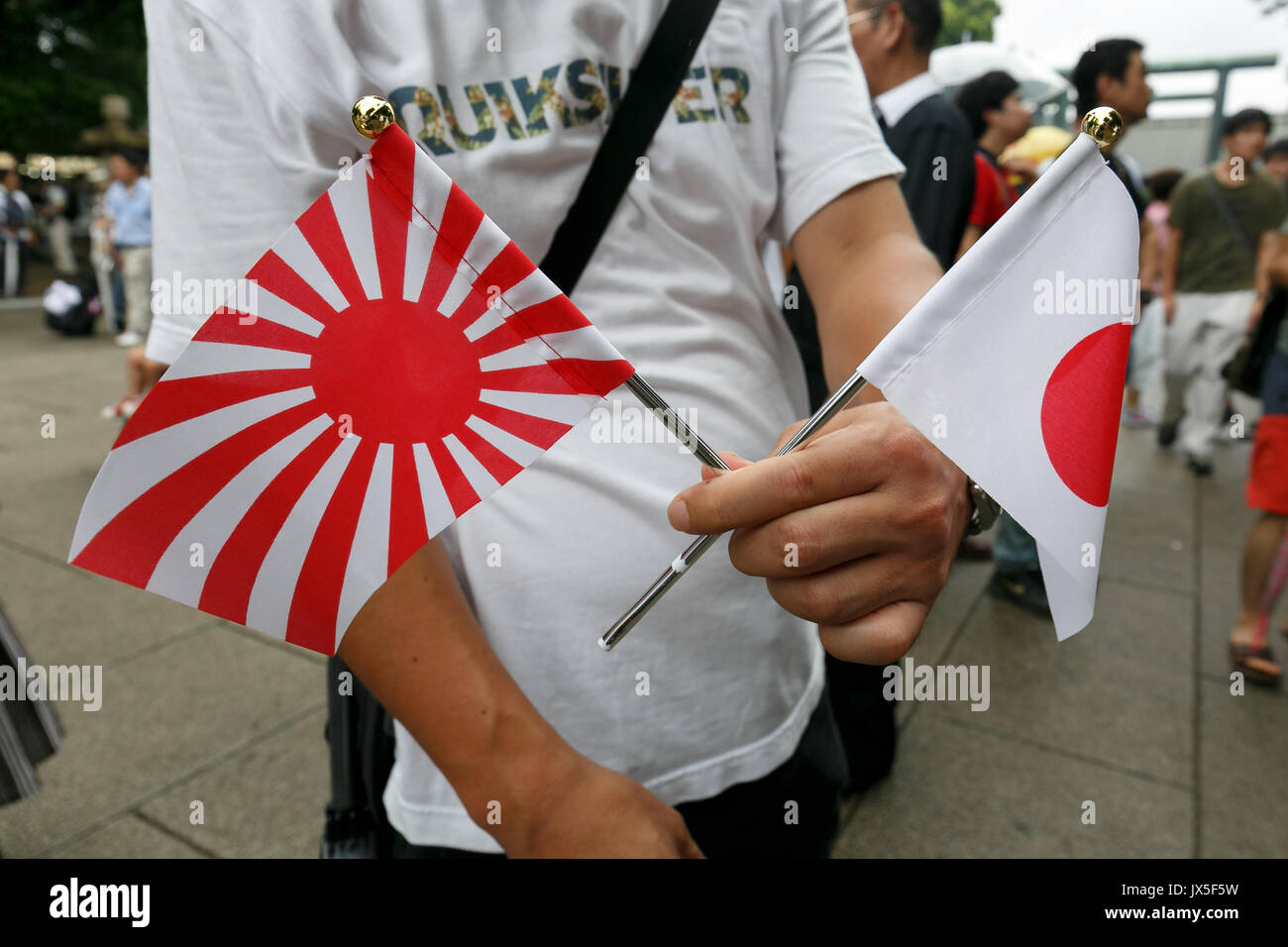 Tokyo, Japan. 15th Aug, 2017. A man holds war flags of the Imperial Japanese Army to pay his respects to the war - Stock Image