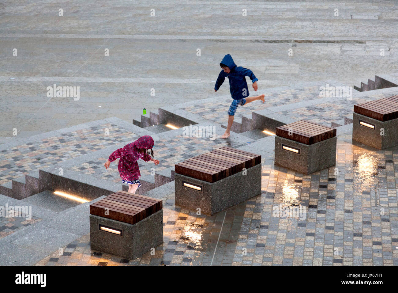 Children playing in the rain at the Piece Hall, Halifax, West Yorkshire - Stock Image