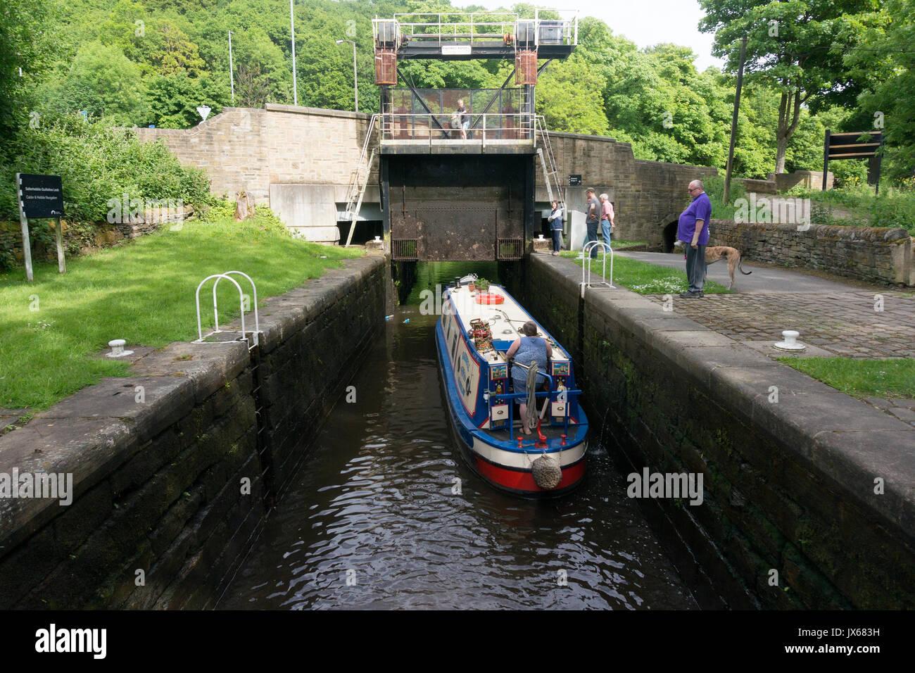 Narrowboat passing through Salterhebble locks on the Calder & Hebble Navigation, Halifax, West Yorkshire - Stock Image