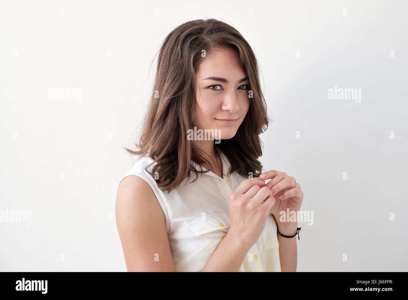 Shy and beautiful young girl looks down - Stock Image
