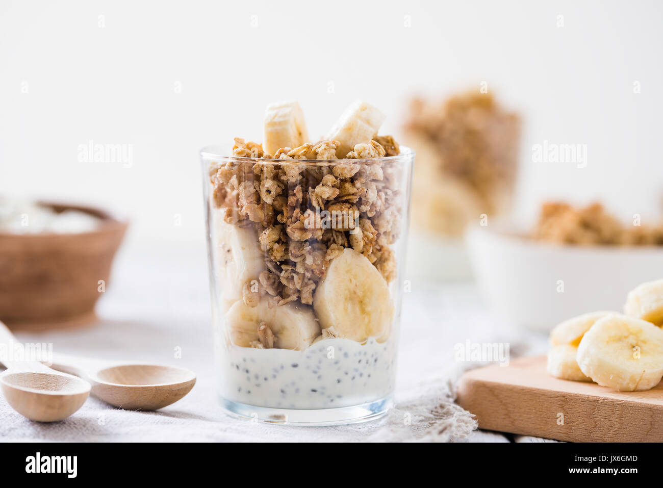 Chia pudding parfait, layered yogurt with banana, granola. Healthy breakfast concept on white wooden table - Stock Image