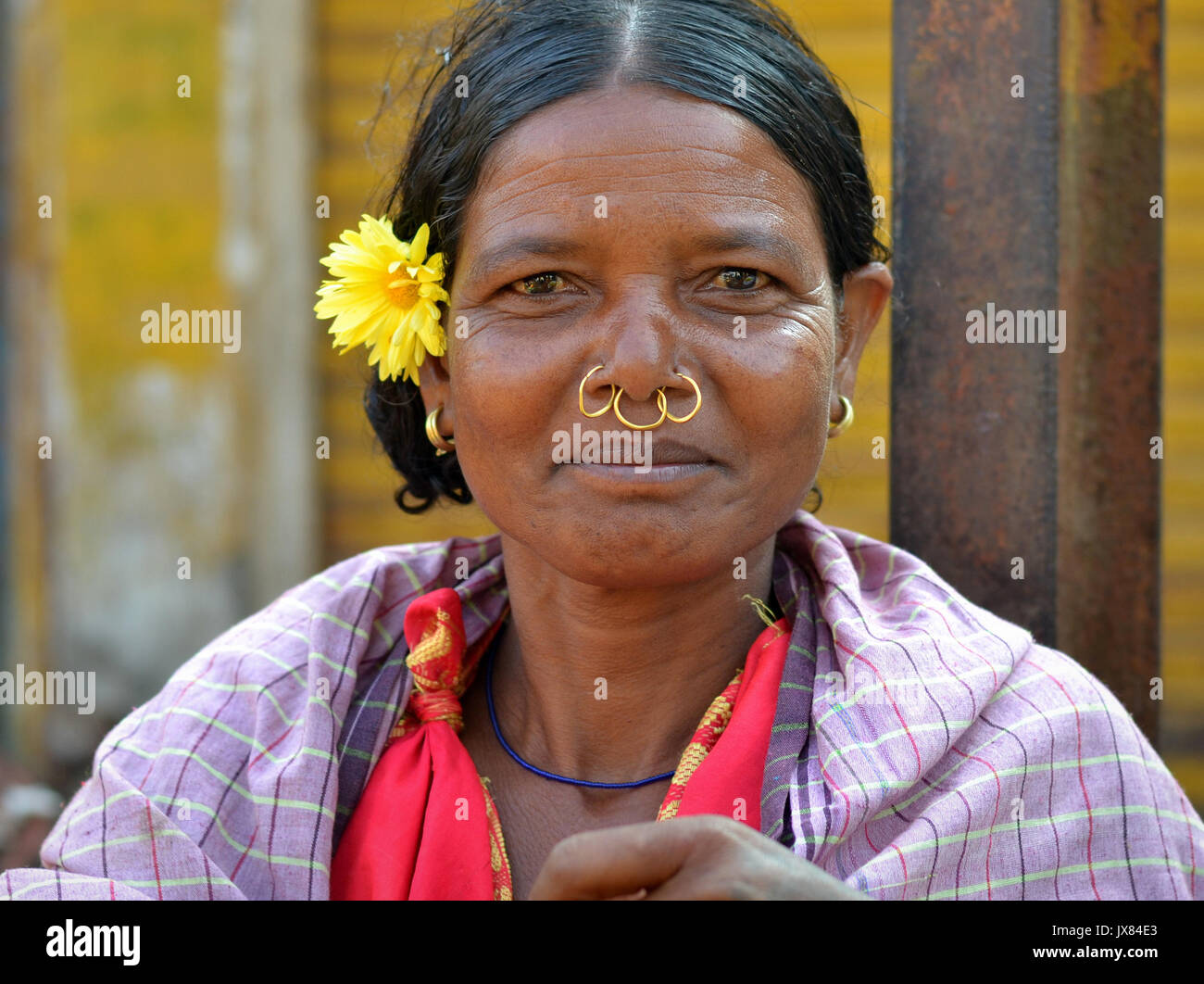 Closeup street portrait (outdoor headshot, full-face view) of a mature Indian Adivasi woman with three golden tribal - Stock Image