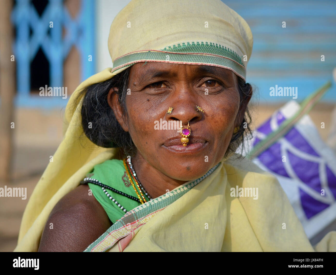 Closeup street portrait (outdoor headshot, full-face view) of a mature Indian Adivasi market woman with two nose Stock Photo
