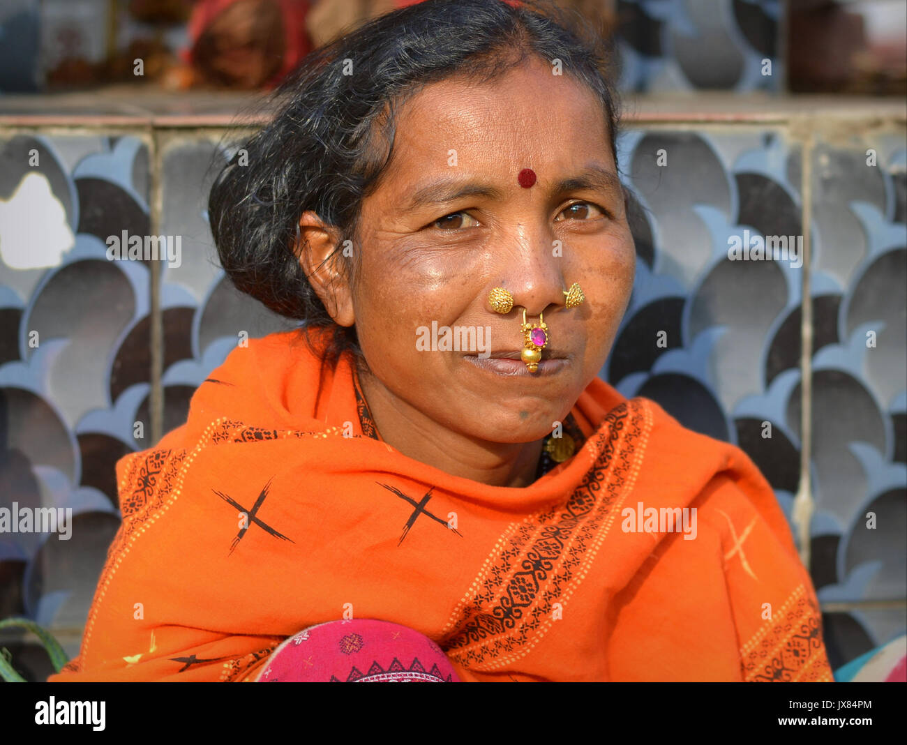 Closeup street portrait (outdoor headshot, three-quarter view) of a mature Indian Adivasi market woman with two Stock Photo