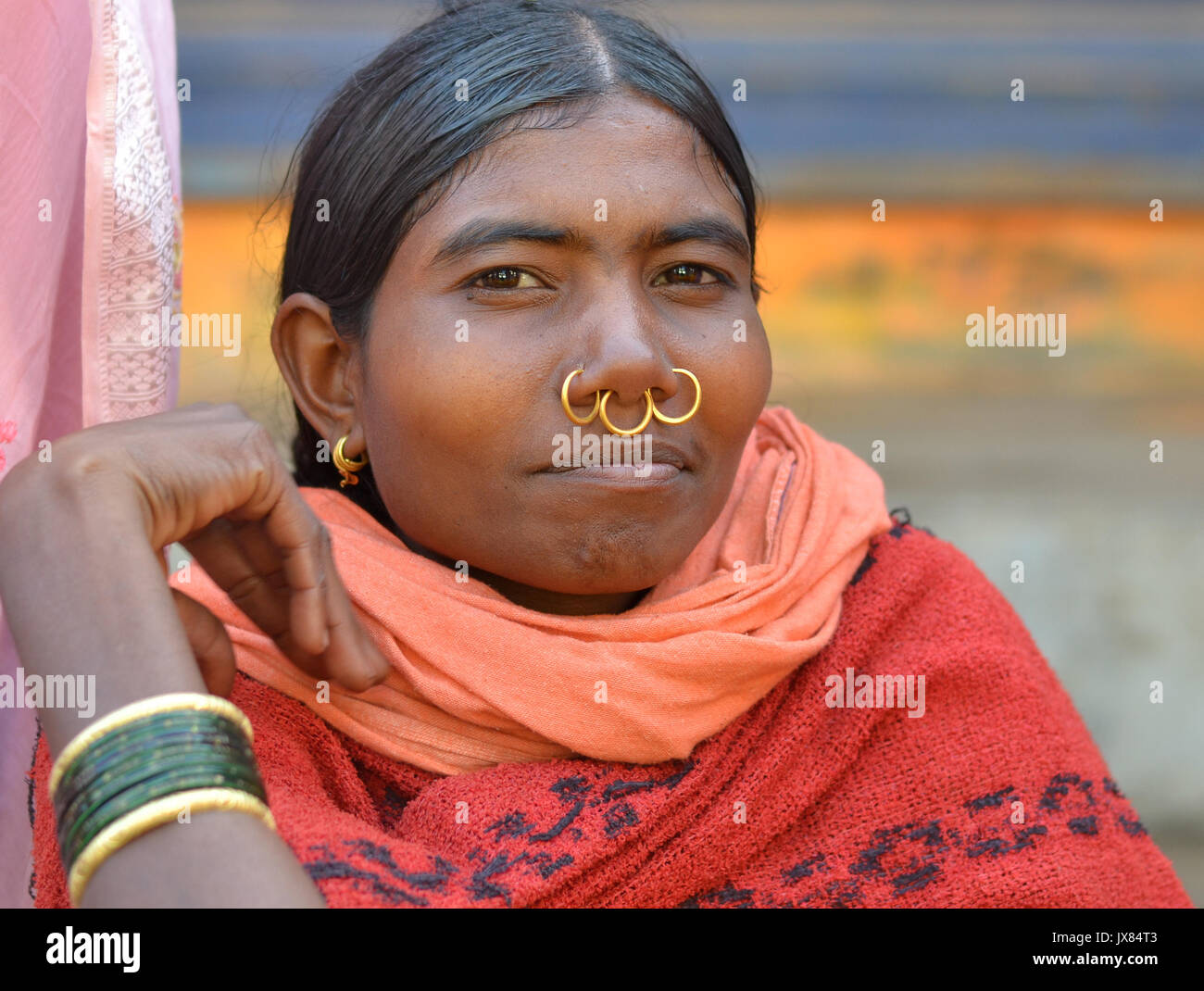 Closeup street portrait (outdoor headshot, three-quarter view) of a young Indian Adivasi market woman with three Stock Photo