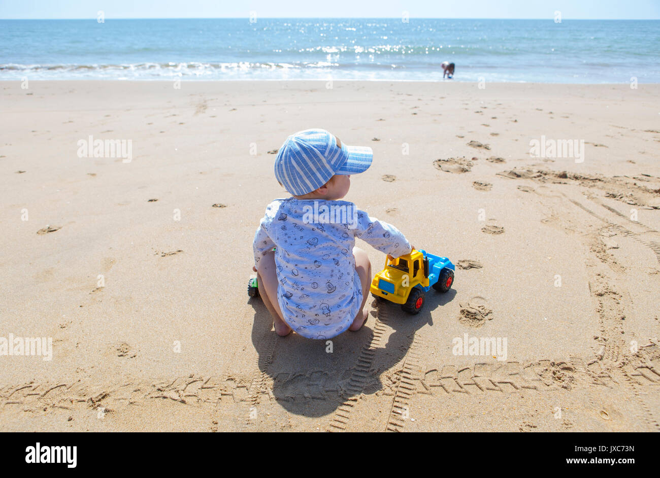 Baby boy playing on the sand while his sister run beside beach shore. El Rompido, Cartaya, Huelva, Spain - Stock Image