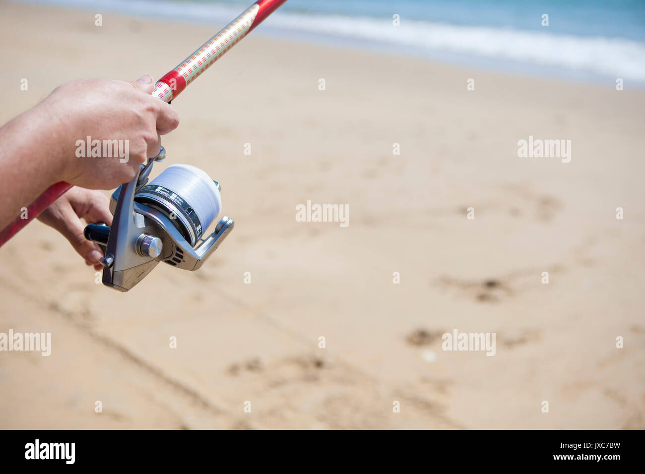 Folding the fishing line. Sea angling sport at the beach - Stock Image