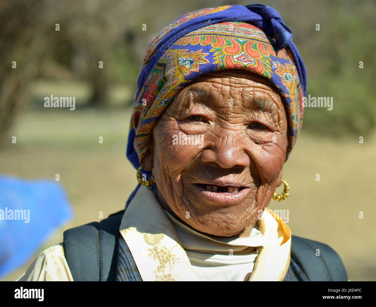 Closeup street portrait (outdoor headshot, full-face view) of an old Sherpa woman with traditional golden earrings; Stock Photo