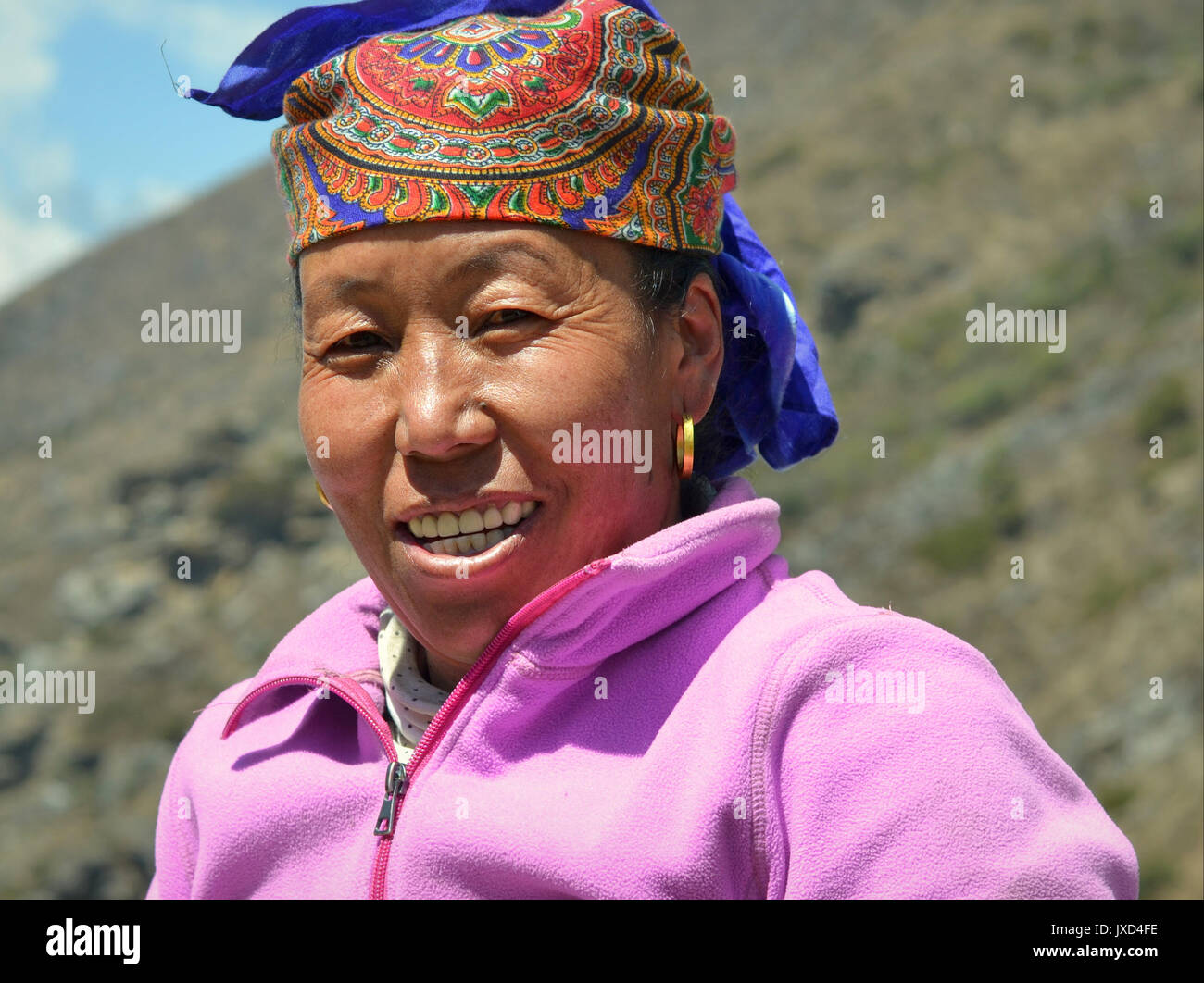 Closeup street portrait (outdoor headshot, three-quarter view) of a middle-aged Sherpa woman with traditional golden Stock Photo