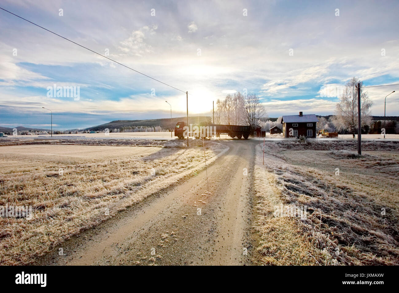 Truck driving on a country road past a wooden house on a frosty autumn morning in Sweden. - Stock Image