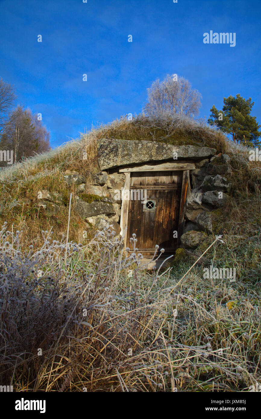 Wooden door to a traditional root cellar used for storing food supplies at a low temperature and steady humidity - Stock Image