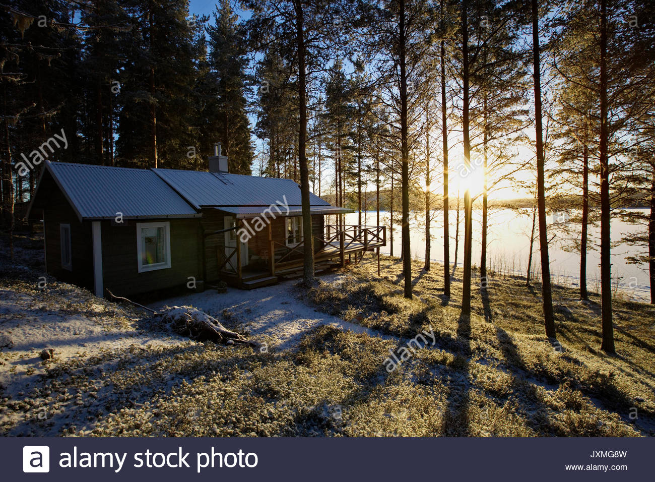 A wooden cottage is standing at the shore of a frozen lake. - Stock Image