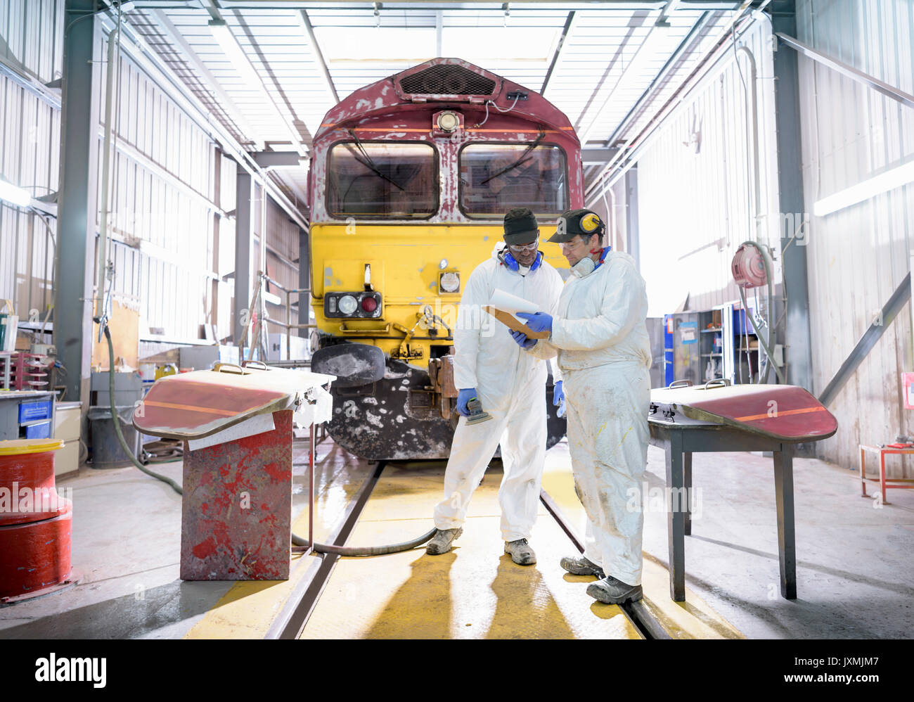 Painters in paintshop with refurbished locomotive in train works - Stock Image