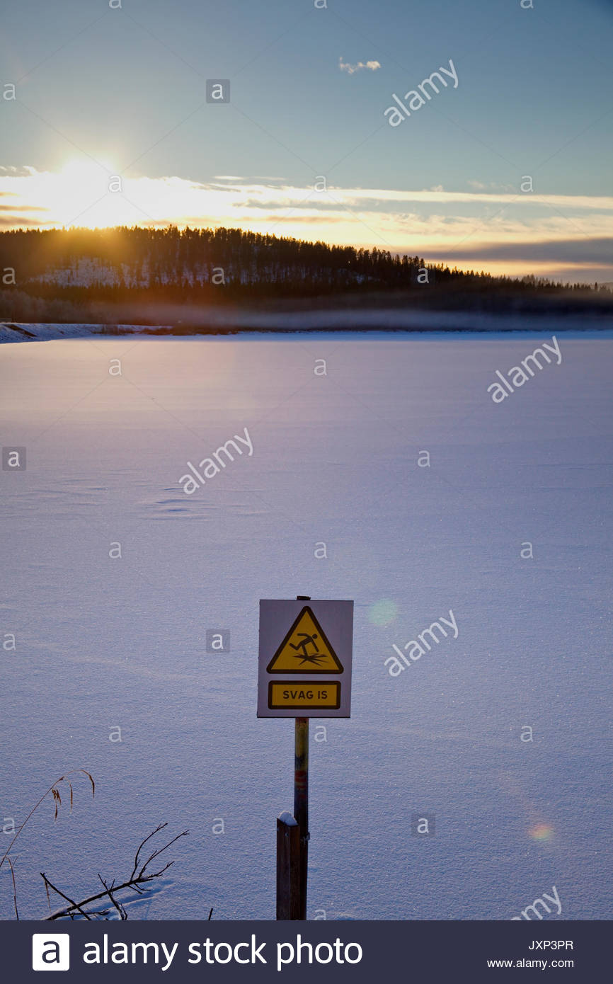 Frozen lake at dusk with a Swedish warning sign. - Stock Image