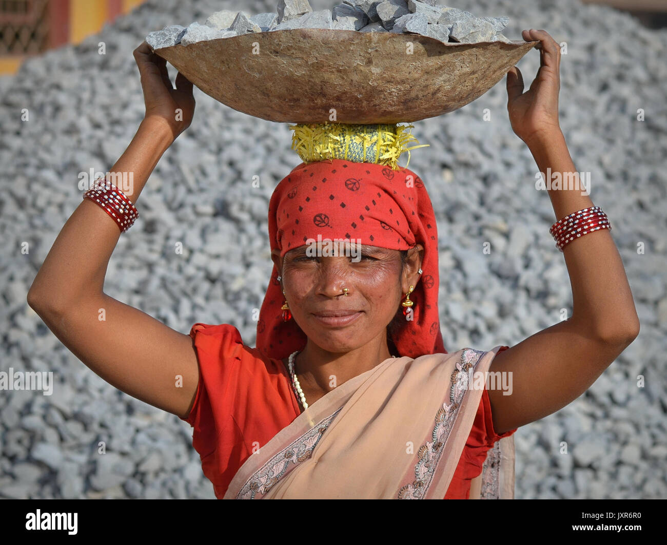 Closeup street portrait of a sari-clad mature Indian Adivasi tribal woman, carrying on her head a metal bowl with Stock Photo