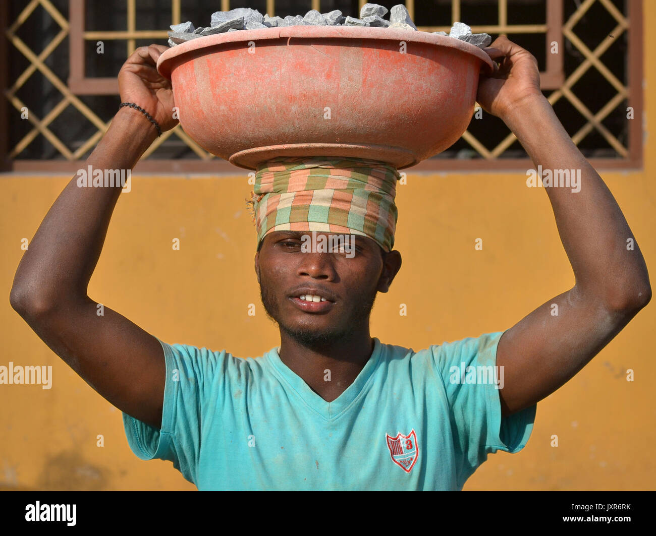 Closeup street portrait of a young Indian Adivasi tribal man, carrying on his head a plastic bowl with crushed rocks - Stock Image