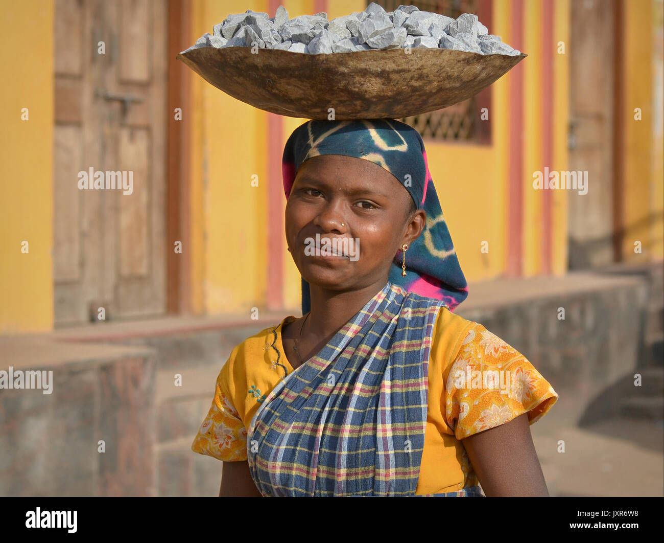 Closeup street portrait of a sari-clad young Indian Adivasi tribal woman, balancing on her head a metal bowl with Stock Photo