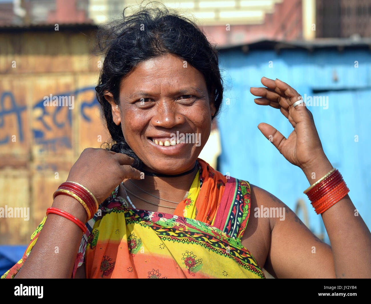 Closeup street portrait of a smiling and laughing mature Indian Adivasi woman, doing her hair with both hands (...and - Stock Image