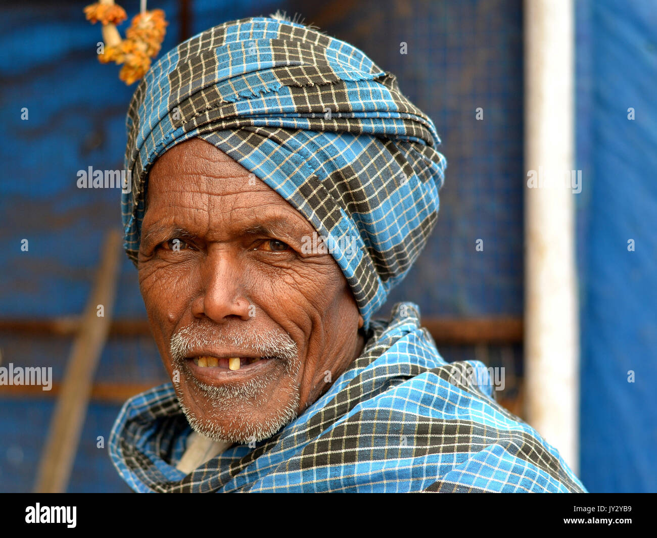 Closeup street portrait of an old Indian Adivasi man, wearing a blue-checkered turban. - Stock Image