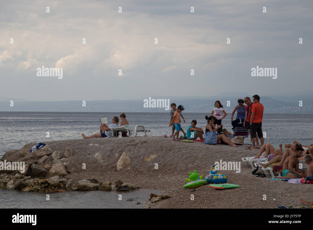 People are seen relaxing on a beach on the island of Krk, Croatia on 24 July, 2017. - Stock Image