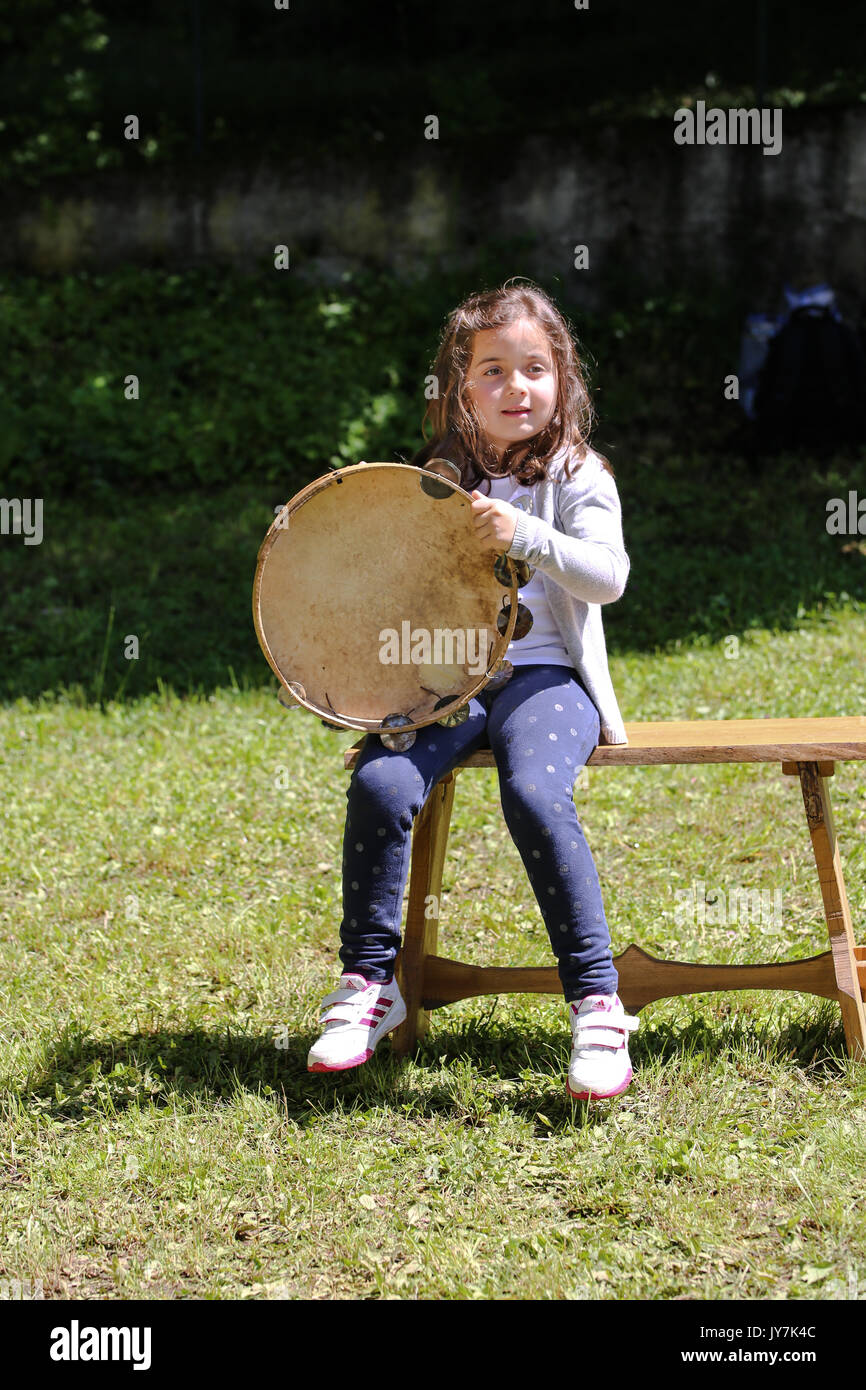 Little girl, sitting on a bench, plays a tambourine - Stock Image