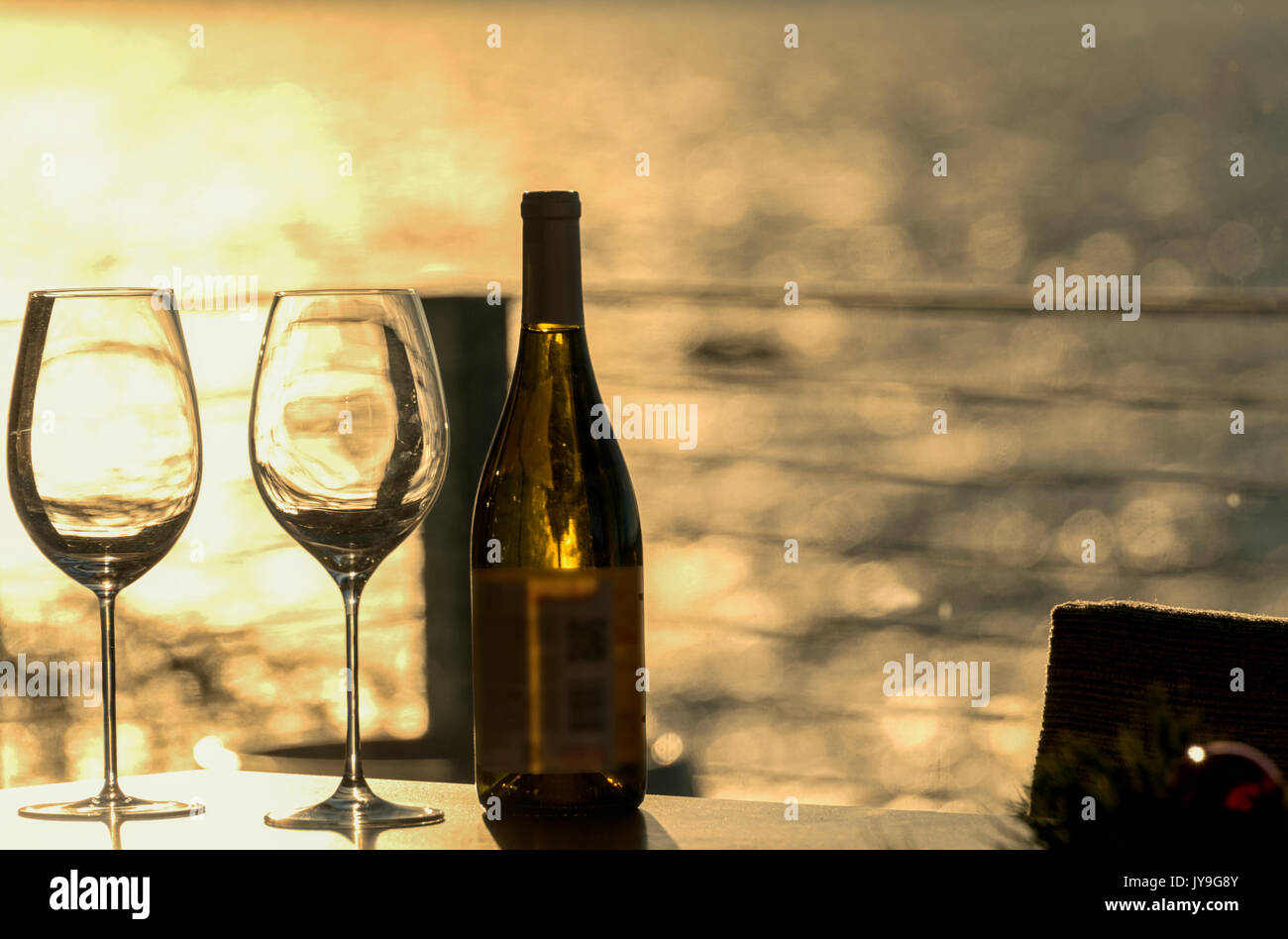 Two empty wine glasses with a bottle on a beach home table with late day sun lighting the water in background. - Stock Image
