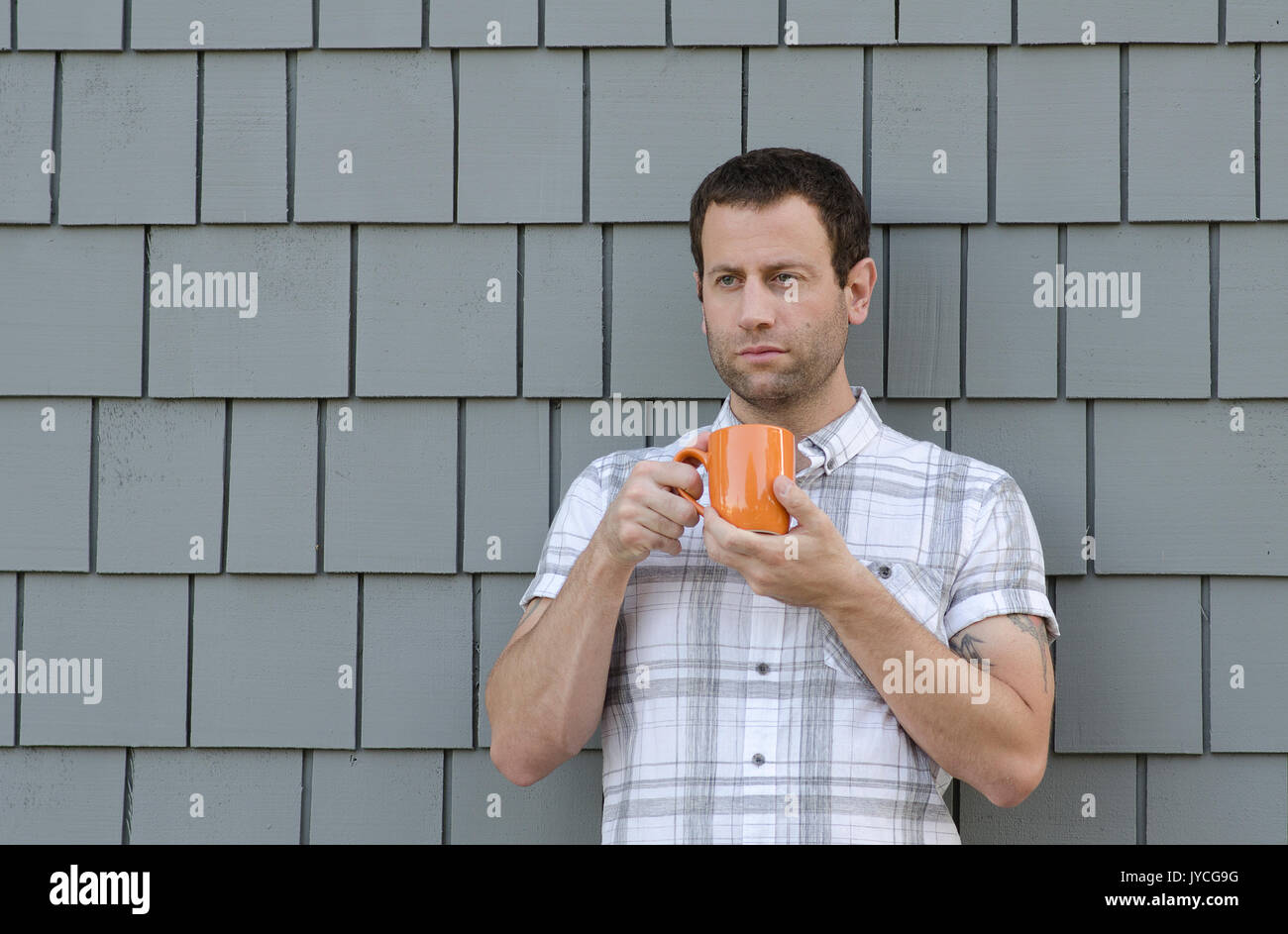 Man holding an orange coffee cup with two hands with a gray background. - Stock Image