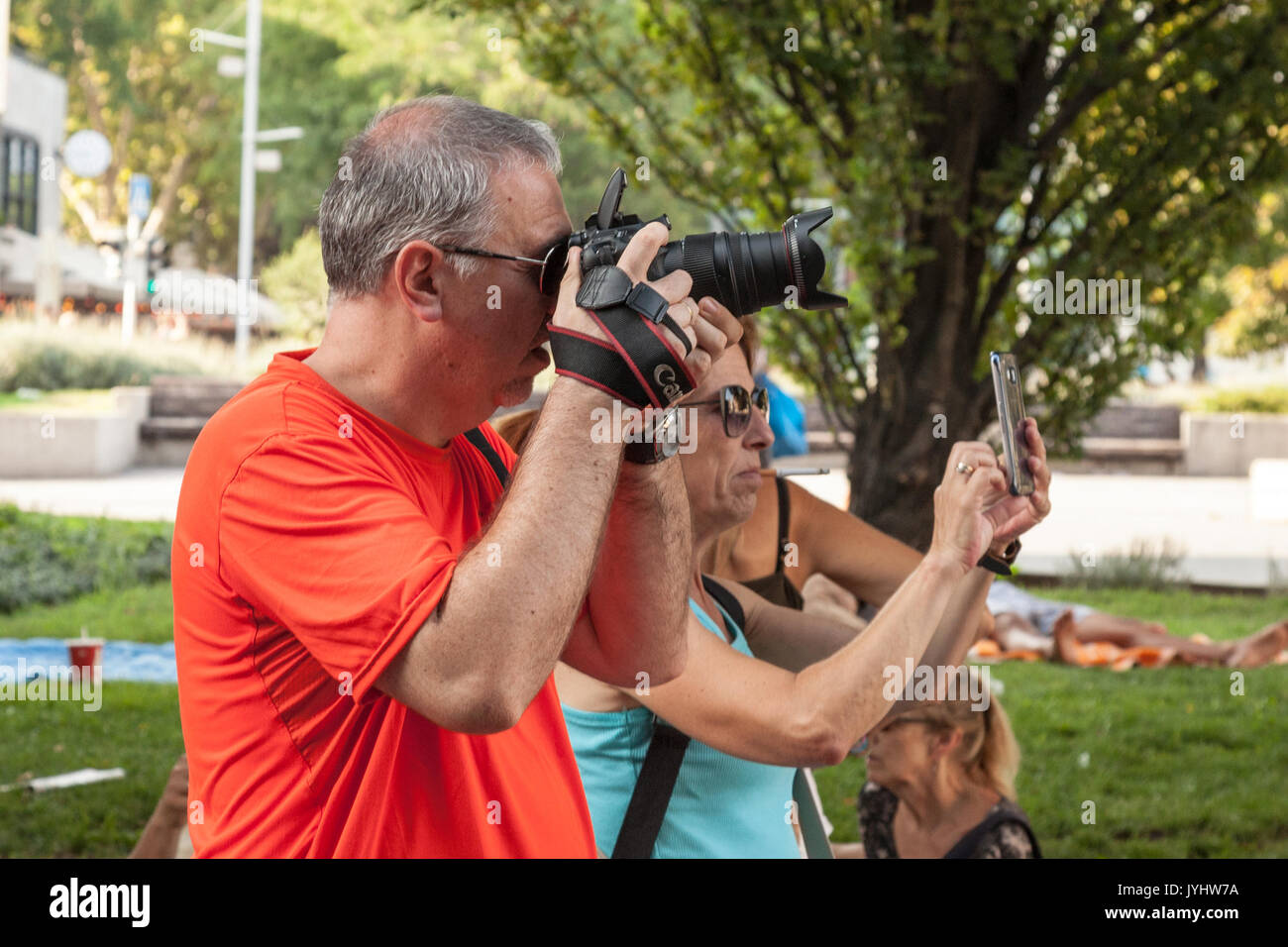 BUDAPEST, HUNGARY - AUGUST 11, 2017: Two people taking pictures in a Budapest park, one using a semi professional - Stock Image