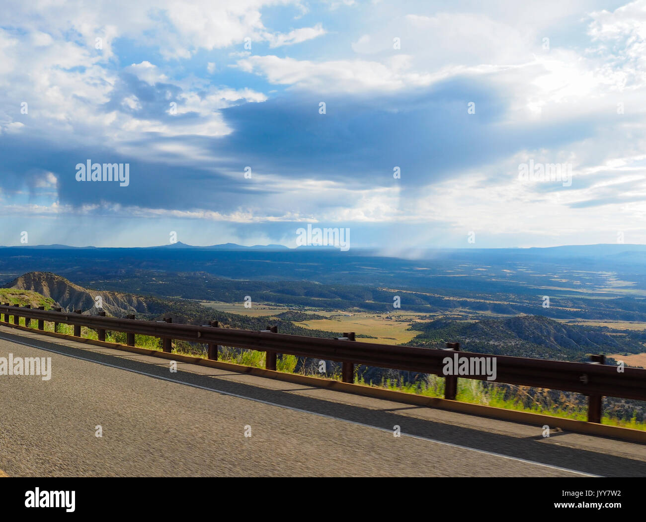 Local rain showers from cumulus nimbus clouds are falling onto the plains near the Mesa Verde high plateau at Mesa - Stock Image