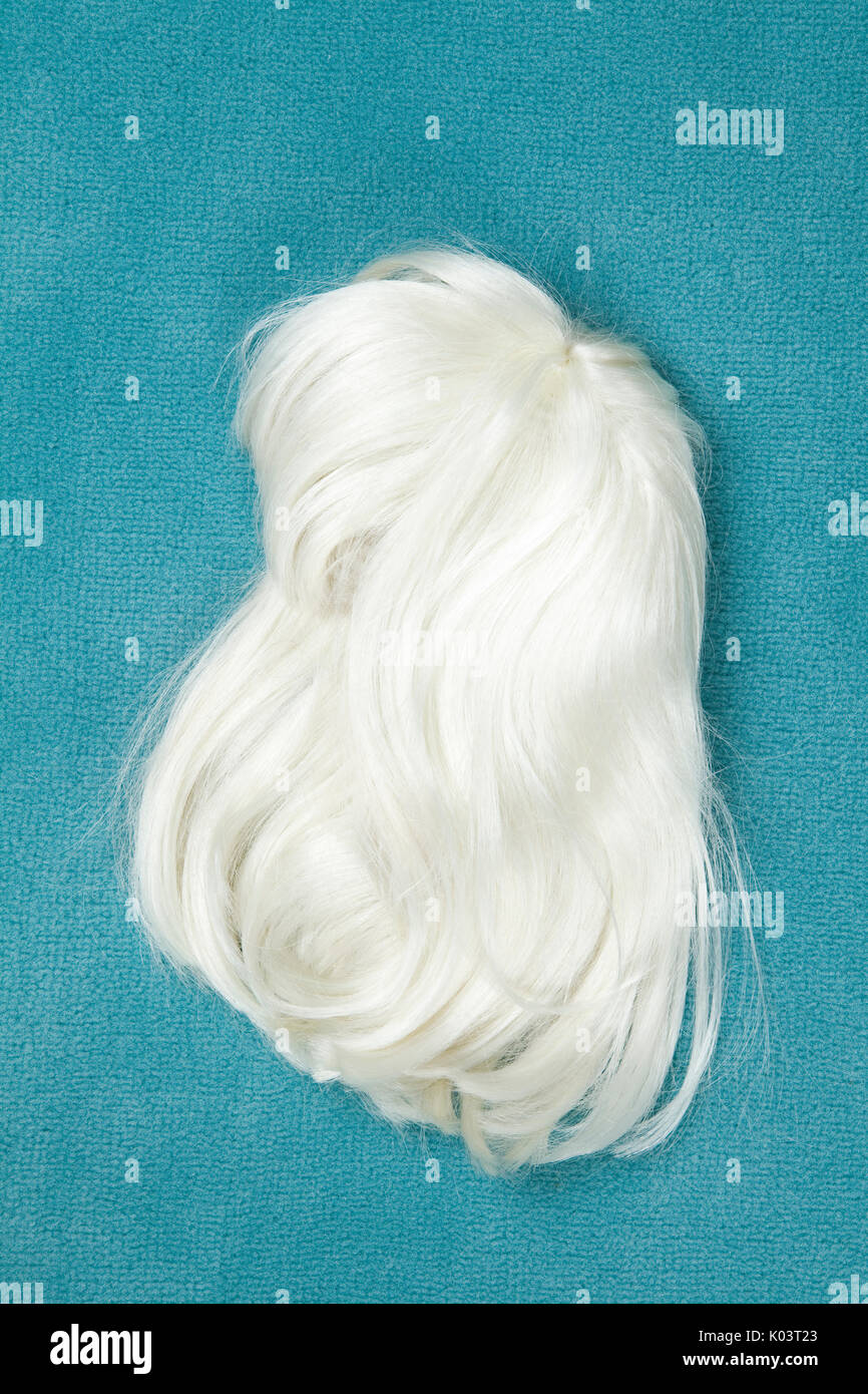 A wig thrown on the floor, on a turquoise carpet. Minimal color still life photography - Stock Image