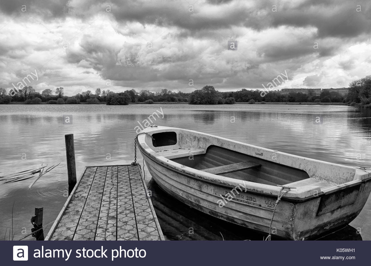 A black and white image of a rowing boat moored to a pontoon on a lake in Bourton on the water in the Cotswolds - Stock Image