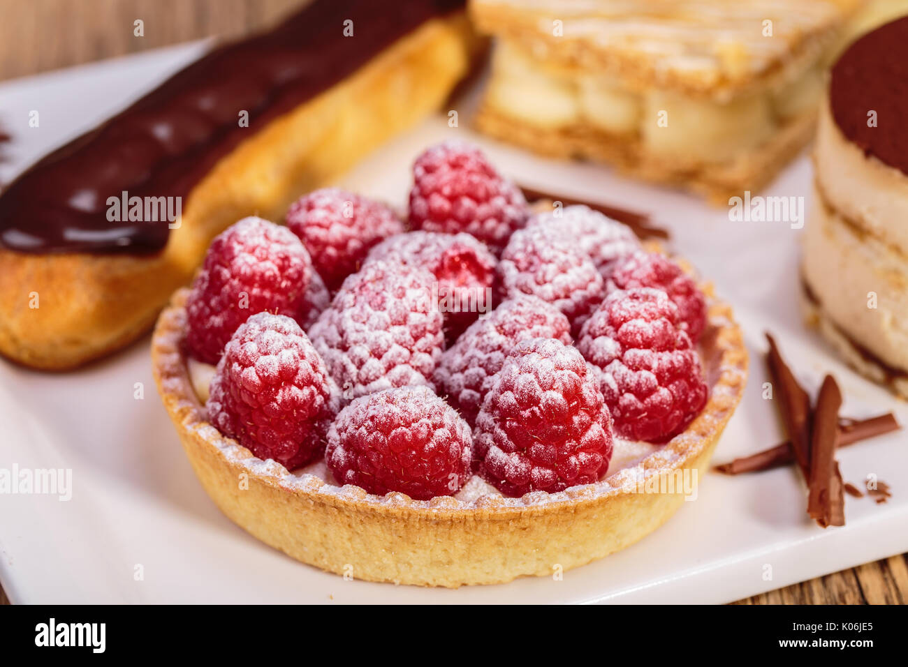close up shot of Delicious raspberry mini tarts with fresh raspberries and icing sugar - Stock Image