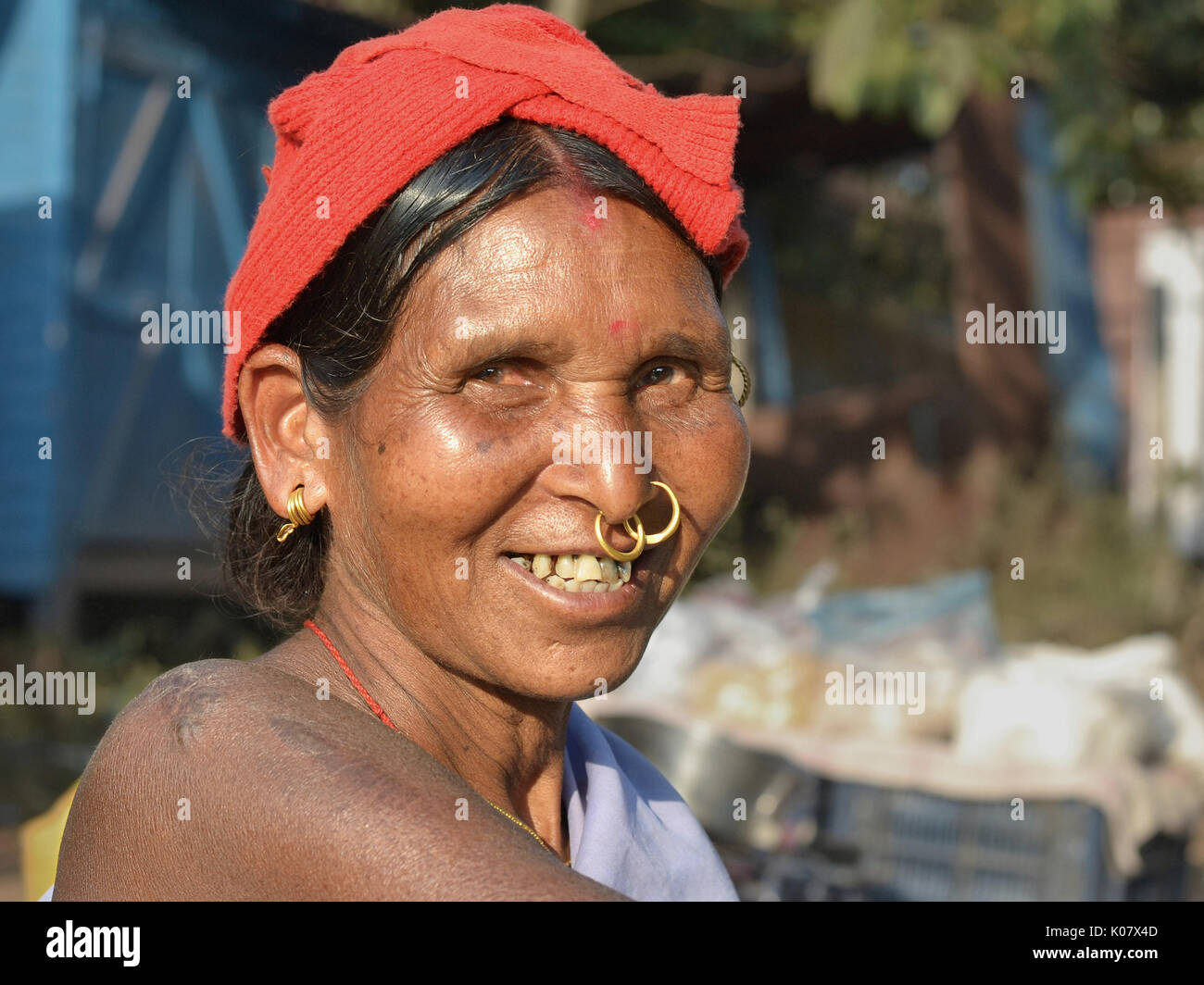 Elderly Indian Adivasi market woman with two golden nose rings and distinctive tribal earrings. Stock Photo