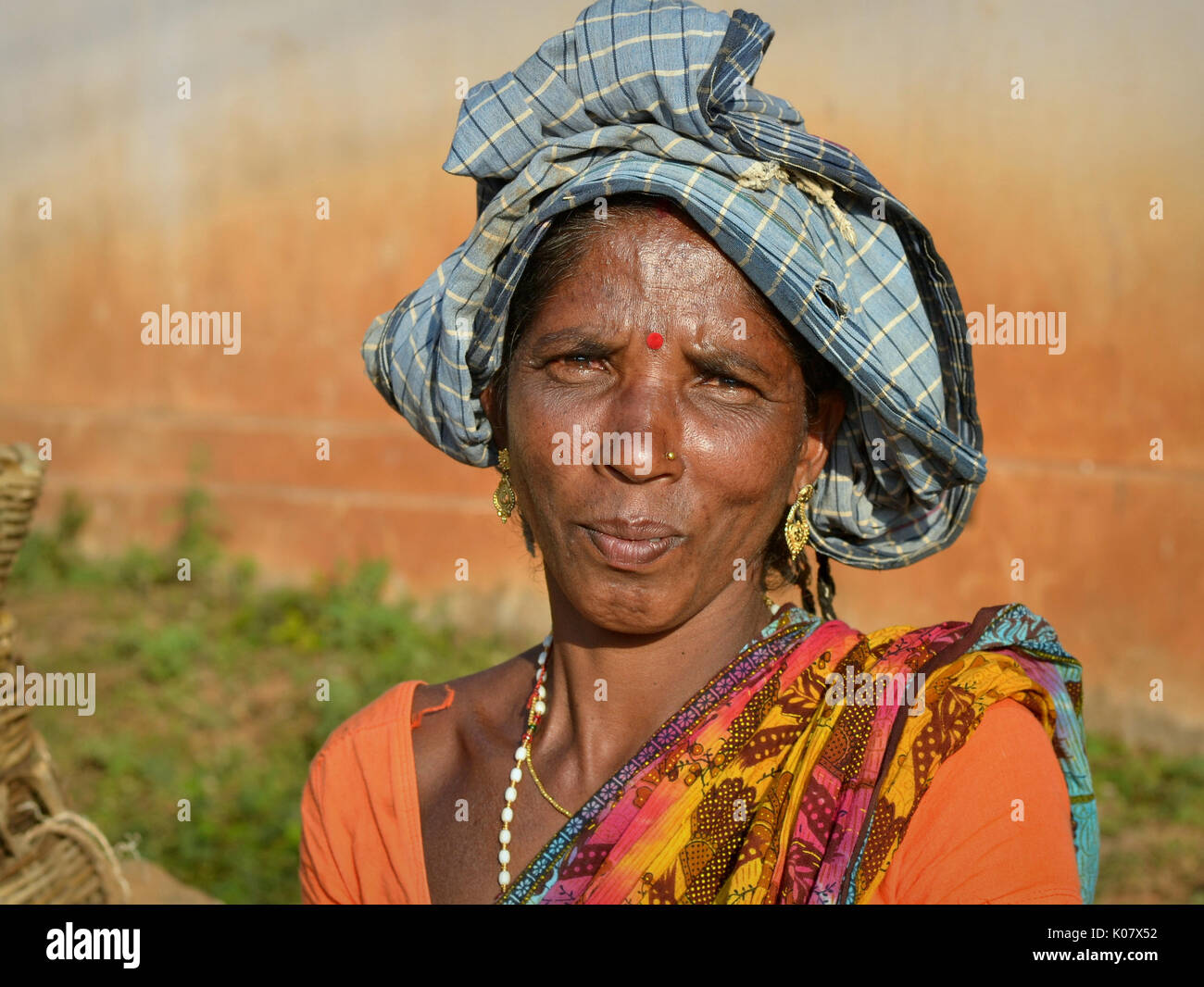 Middle-aged Indian Adivasi market woman with precious golden drop earrings. - Stock Image