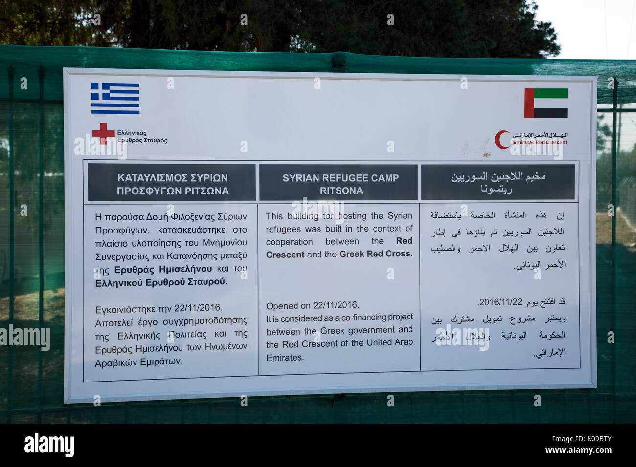 A sign at the entrance to Ritsona Refugee Camp in Greek, English and Arabic tells of cooperation of Greek Red Cross - Stock Image