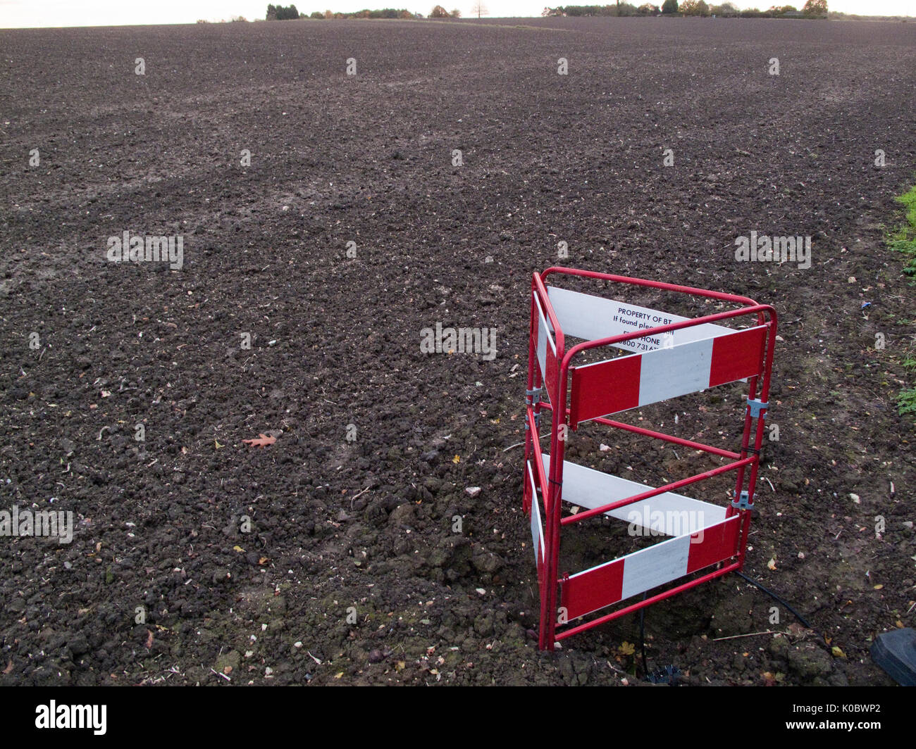 British Telecom hole in the ground by a freshly harrowed field - Stock Image
