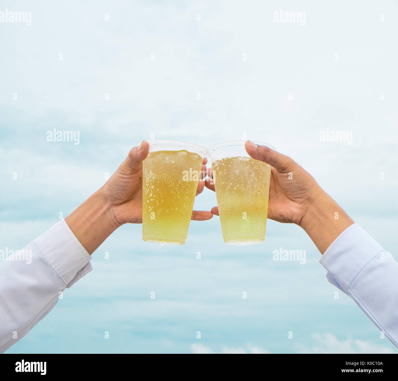 Celebration party, hands hold beverage beers with plastic glasses and cheer for success have beautiful sky as background - Stock Image