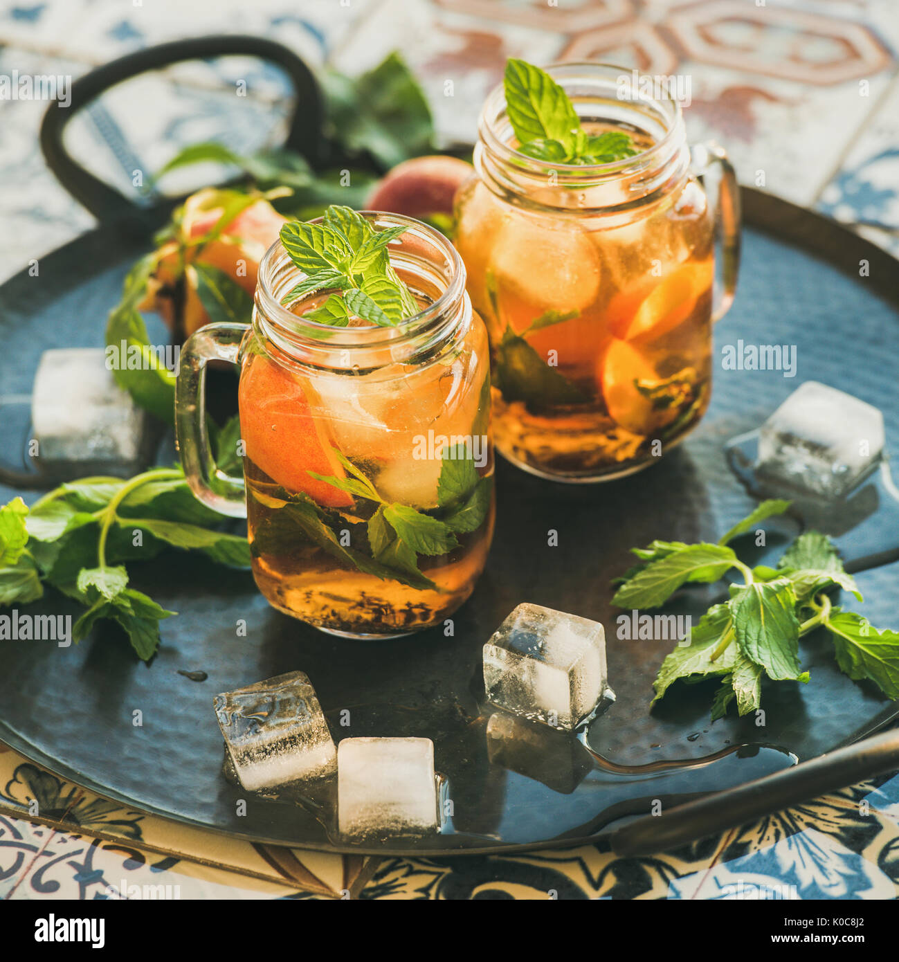 Summer refreshing cold peach ice tea with mint, square crop - Stock Image
