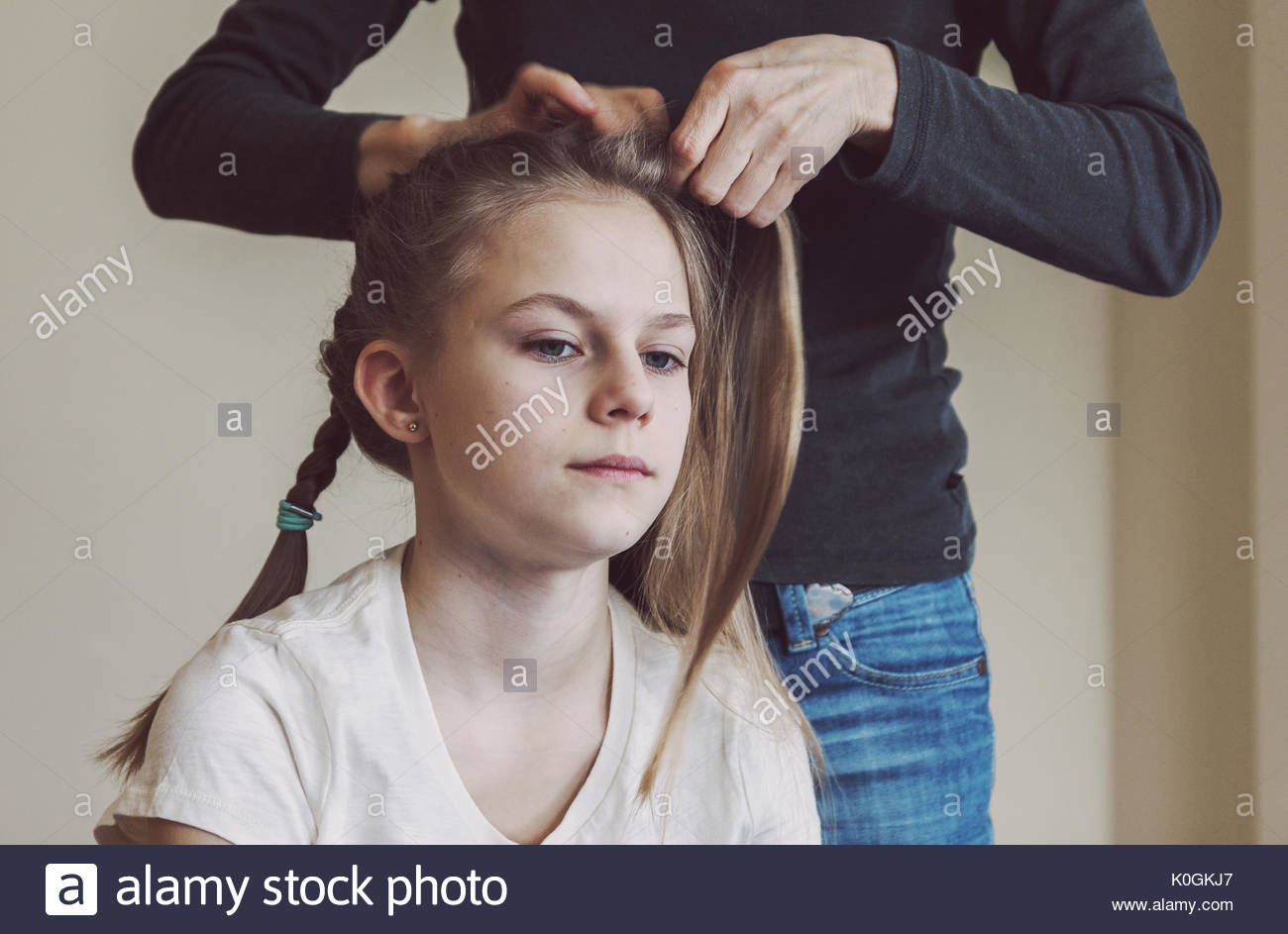 Mother braiding young girls hair. Real life portrait picture of caucasian teen girl with deliberate warm mate filter - Stock Image