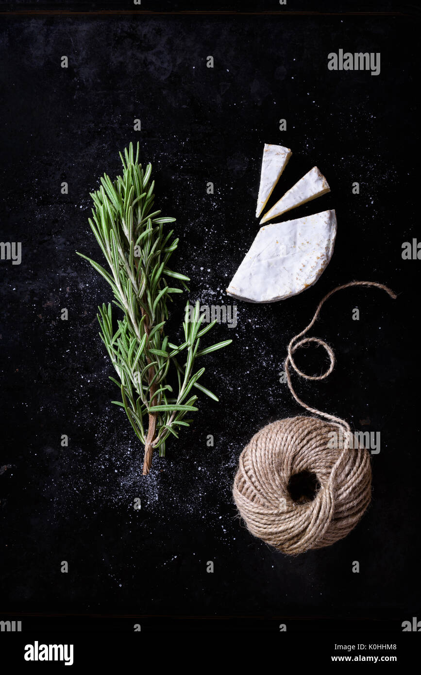 Camembert cheese with rosemary herbs. French snack. Above view, dark background. - Stock Image