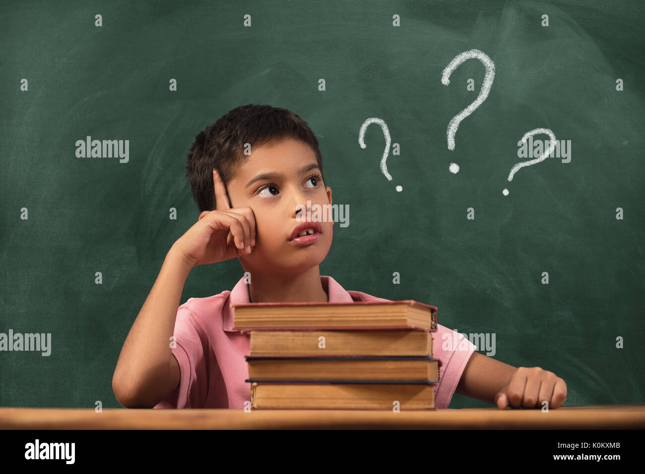Boy with doubts and thoughts in class. Portrait of male child thinking against question marks on blackboard - Stock Image