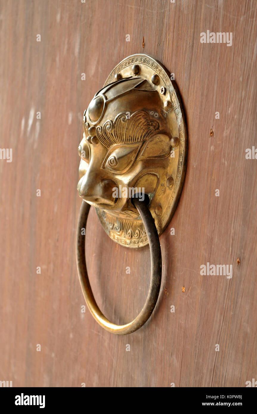 Lion head door handle. Installed on the doors of art in China. - Stock Image